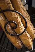 Paris, France. Bread baguettes in a wrought iron display outside a bakery.