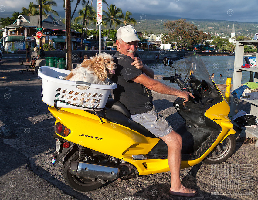 A man with his dog on a motorcycle by the pier in Kailua-Kona, Big Island of Hawai'i.