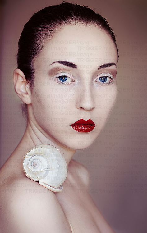 Portrait of a young girl with dark combed back hair, blue eyes, red lips and pale skin, with a snail shell on her shoulder with simple background, looking into camera.