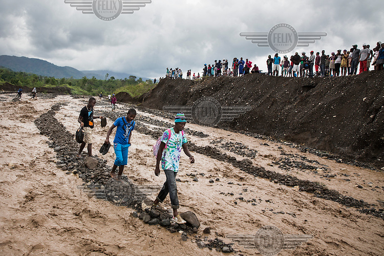 People carefully make their way across La Digue River after a crucial bridge collapsed as a result of Hurricane Matthew. The collapse of the bridge meant emergency responders where unable to reach the worst hit southwestern peninsula of the island. Hurricane Matthew, the first category 5 Atlantic hurricane since 2007, hit the island on 4 October 2016. Winds of up to 230km/h (145mph) tore across the worst affected areas, mainly in the south of the island, killing around over 1,000 people and leaving hundreds of thousands in need of assistance.