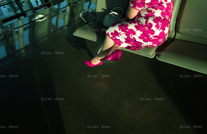 A woman wearing a red flower dress at the airport Shanghai, China in April 2008...