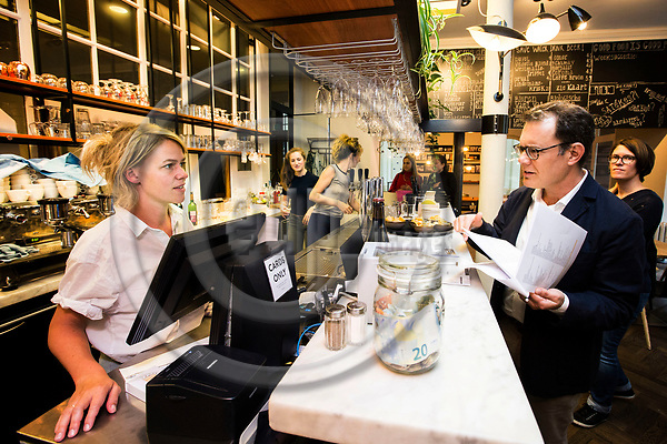 BRUSSELS - BELGIUM - 21 August 2017 -- British EU-Correspondent for the New York Times, James KANTER, wants to change his nationality to the Belgium one because of Brexit. He has to study and learn to speak Flemish for the integration test he has to undergo. Practising his Flemish with waitress Marjolijn in the cafe Markten. -- PHOTO: Juha ROININEN / EUP-IMAGES