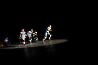 Skaters take a lap in the spotlight as their team is introduced before a roller derby bout in Wilmington, Massachusetts. Roller derby is an American contact sport, popular with young women, which combines both athleticism and a satirical punk third-wave feminism aesthetic.