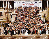 "United States Vice President George H.W. Bush and all the White House staff members with ""Get Well Soon Mr. President"" sign in front of Old Executive Office Building, next door to the White House in Washington, D.C. on Tuesday, April 7, 1981. .Mandatory Credit: Bill Fitz-Patrick - White House via CNP"