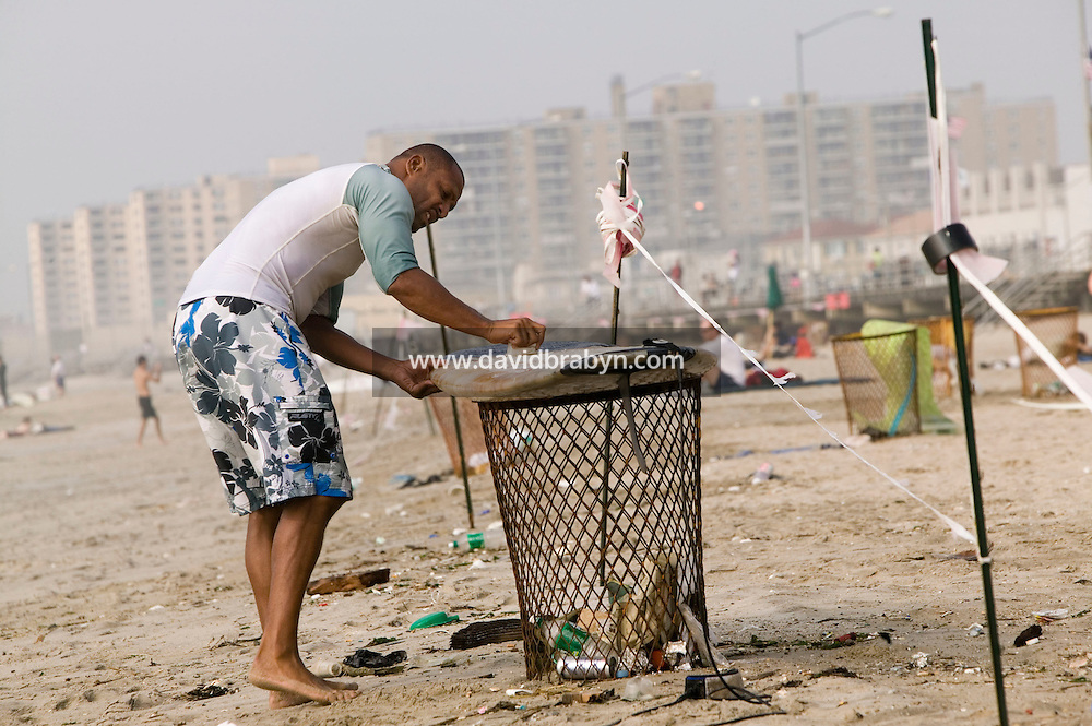 A surfer uses a trash can for support as he waxes his board at Far Rockaway beach in New York, United States, 17 September 2005. Photo Credit: David Brabyn.