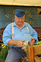 Colonial broomsquire Robert Aborn, makes a pot scrubber 18th century style,  by peeling a piece of yellow birch at the Nathan Hale Homestead during a Revolutionary War encampment and muster, Coventry, Connecticut, USA.