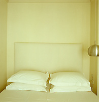 The all-white bedroom has a simple bed with a headboard and plain bed linen
