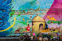 Colombian vendors sell fruits in front of a large mural in Getsemaní, a popular artistic neighborhood in Cartagena, Colombia, 12 December 2017. With the peace agreement, ending a 52-year civil conflict and promising political stability, together with rapid economic growth and unexploited tourism potential, Colombia has truly become a holiday destination. Cartagena, a UNESCO World Heritage site on the tropical Caribbean coast, plays the primary role in Colombia's tourism renaissance. The historic sites from the Spanish colonial times are being restored, private investments are visible throughout the city and an increased number of local people benefit from the boom of the travel related services.