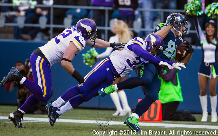 Seattle Seahawks tight end Zach Miller is brought down by Minneosta Vikings safety Jamarca Sanford (33) after catching a pass against the Minnesota Vikings at CenturyLink Field in Seattle, Washington on  November 17, 2013.  The Seahawks beat the Vikings 41-20.  ©2013.  Jim Bryant. All Rights Reserved.