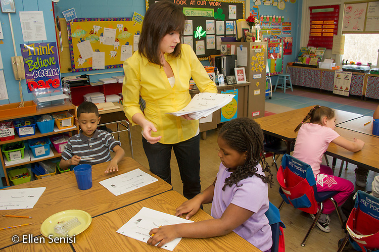 MR / Schenectady, New York. Yates Arts-in-Education Magnet School (urban public school). First grade classroom. Teacher passes out worksheets for students to record results. The class is doing a science lesson which requires them to observe and record sensory properties of physical objects including seeds and dried beans. MR: Whi11, Bel5, Cov1. ID: AM-g1w. © Ellen B. Senisi.