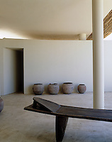 A row of South African pots stands against one of the external floating walls that typify the property