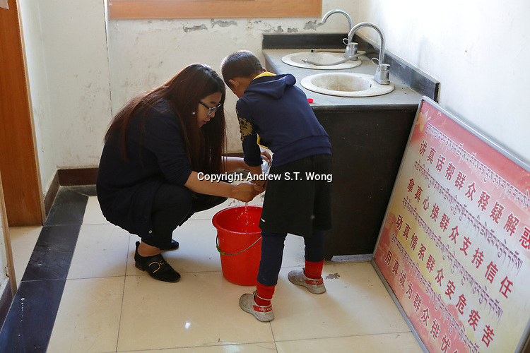 Lhasa, Tibet, China - Tibetan educator Deqingyuzhen washes the dirty hands of a poor students during free classes at a community centre in Lhasa, September 2018.