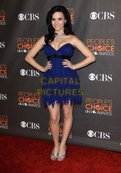 DEMI LOVATO.Arrivals at the 2010 People's Choice Awards held at the Nokia Theater L.A. Live in Los Angeles, California, USA. .January 6th, 2010 .full length blue strapless layers layered dress black sash silver shoes hands on hips .CAP/ADM/KB.©Kevan Brooks/AdMedia/Capital Pictures.