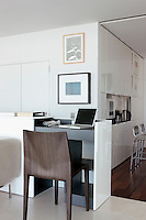 The design of the living space is ingenious, such as this desk area concealed in a lacquered room partition
