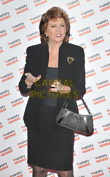 Cilla Black.The Hidden Gems Photography Gala Auction in aid of the Variety Club Children's Charity, St. Pancras Renaissance Hotel, Euston Rd., London, England,  .November 30th, 2011.half length jacket black top skirt brooch heart gold mouth open hand bag purse .CAP/CAN.©Can Nguyen/Capital Pictures.