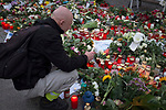 A man with a candle kneels before a carpet of floral tributes lying outside the French embassy in Berlin. The flowers and other tributes were laid by people in remembrance of those killed in the terrorist attacks on Paris by Islamic State militants. The attacks on Friday 13th November took place across six different sites in the French capital and left more than 130 people dead.