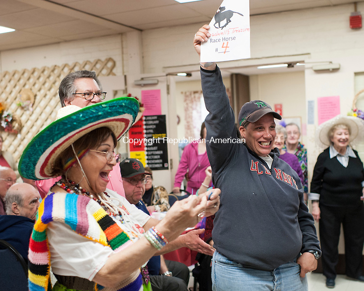 "NAUGATUCK, CT-1 May 2015-050115EC06-  Maritza Bok-Lopez celebrates after being declared the winning ""jockey"" during Kentucky Derby Day at the Naugatuck Senior Center. Next to her is Vickie Rodriguez, who had a winning ticket. This is the tenth year the senior center marked the Kentucky Derby with it's own friendly competition. Members volunteered to be jockeys and were assigned a horse number. A roll of the dice determined if they advanced to a winning position. The senior center was packed with fancy hats and a Kentucky themed dinner. Members of the U.S. Army handed out roses. Erin Covey Republican-American"