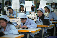 Factory workers sewing with the sewing machine at the factory in Guangzhou, China..17-JAN-03