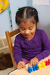 Education preschool 3 year olds girl counting colored plastic bears she has lined up by color