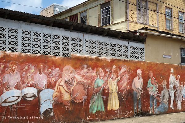 A painted mural of musicians and dancers on a wall in Anse La Raye, St Lucia