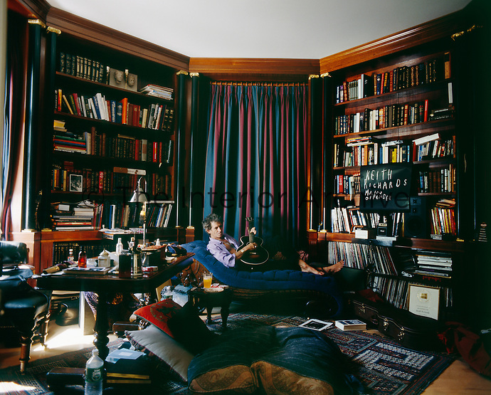 Rolling Stones guitarist Keith Richards, relaxes on a chaise in his octagonal library