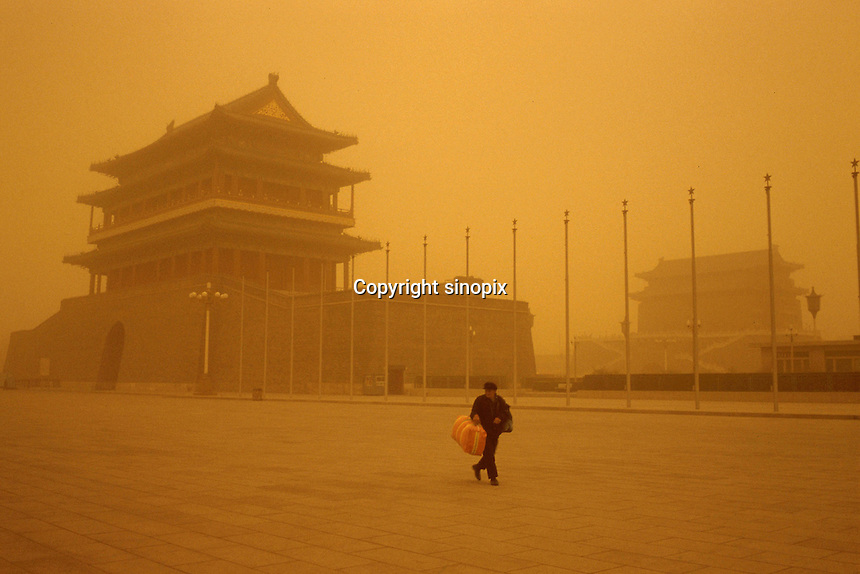 A lone man walks past Qianmen Gate near Tiananmen square in Beijing. When dust storms strike the capital, they turn the sky an amber color and reduce visibility to around a 100 meters. Extensive deforestation and desertification in northern China have fueled the dust storms. Nearly one million tons of Gobi Desert sand blows into Beijing each year...LOU / SINOPIX