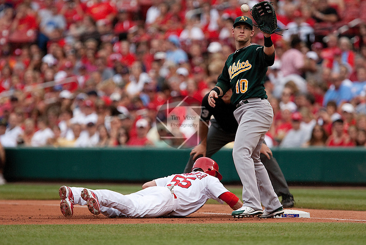 June 19, 2010       St. Louis Cardinals second baseman Skip Schumaker (55) dives safely back to first base, to beat the pickoff throw from the pitcher to Oakland Athletics first baseman Daric Barton (10).  The St. Louis Cardinals defeated the Oakland Athletics 4-3 in the second game of a three-game homestand at Busch Stadium in downtown St. Louis, MO on Saturday June 19, 2010.