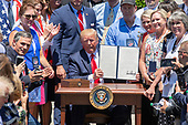 "United States President Donald J. Trump displays the presidential proclamation titled ""Maximizing Use of American-Made Goods, Products and Materials"" after it was signed as he hosts the Third Annual ""Made in America"" Product Showcase on the South Lawn of the White House in Washington, DC on Monday, July 15, 2019.<br /> Credit: Ron Sachs / CNP"