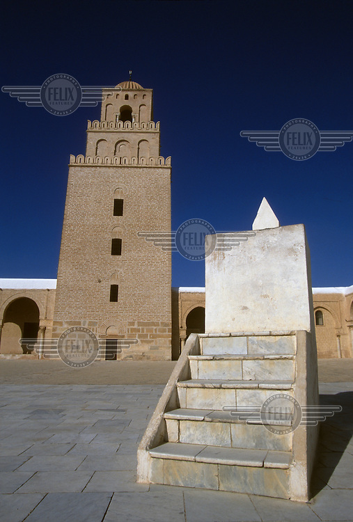 Pulpit in the courtyard of the Mosque of Sidi Oqba (The Great Mosque) in front of the minaret.  Reconstructed in the 8th century, the minaret is the oldest in North Africa...