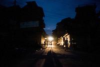 Srinagar, India-August 8, 2010: A Kashmiri family is silhouetted in an alley in downtown Srinagar during a curfew