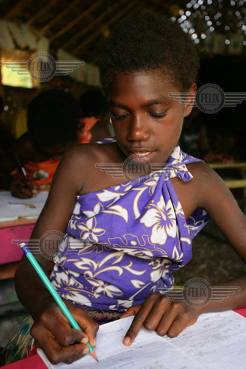 A girl studies in class at Imanaka primary school. The school is supported by UNICEF and follows a French curriculum...