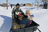 "Monday March 12, 2007   ----   Iditarod air force pilot Danny Davidson and ""Teacher on the Trail"" Kim Slade sit with 5 dropped dogs in a sled being towed to the airport at Kaltag."