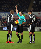 Match referee Michael Oliver (C) shows Allan Nyom of Watford (L) a yellow card for his foul against Neil Taylor of Swansea during the Barclays Premier League match between Swansea City and Watford at the Liberty Stadium, Swansea on January 18 2016