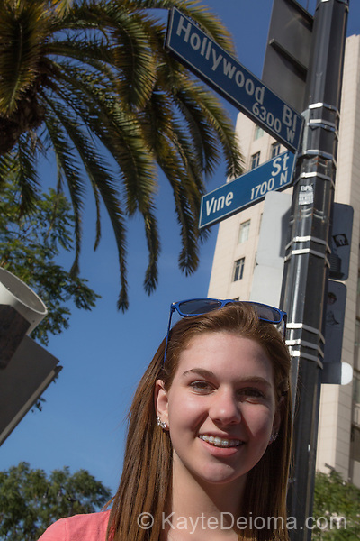 Teen girl in front of the Hollywood and Vine street signs in Hollywood, Los Angeles, CA