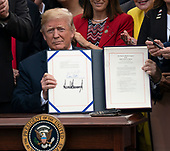 United States President Donald J. Trump displays S. 2372 – VA Mission Act of 2018 during the signing ceremony at the White House in Washington, DC, June 6, 2018. Credit: Chris Kleponis / CNP