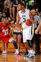 21 January 2012:  FIU guard-forward Dominique Ferguson (3) handles the ball while being defended by FAU guard-forward Jordan McCoy (21) in the first half as the Florida Atlantic University Owls defeated the FIU Golden Panthers, 66-64, at the U.S. Century Bank Arena in Miami, Florida.