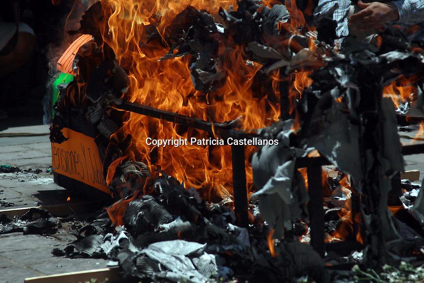 """Oaxaca de Juárez, Oax. 01/05/2016.- Más de 3 mil integrantes de la sección 22 adheridos a la Coordinadora Nacional de Trabajadores de la Educación (CNTE), se movilizaron este 1° de mayo en el marco de la conmemoración del """"Día del Trabajo"""", realizando durante y al final de su marcha protestas radicales como: arrancar propaganda, pintar bardas, quemar publicidad política así como un féretro elaborado de cartón, e intentaron de forma violenta entrar al palacio de gobierno para que les fuera recibido su """"Pliego petitorio anual"""" por el gobernador del estado, Gabino Cué Monteagudo, siendo esta última acción un total fracaso, ya que debido a su brusca forma de hacerse escuchar, las autoridades no les recibieron nada."""
