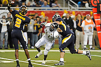 26 December 2010:  FIU linebacker Jarvis Wilson (31) is held by Toledo offensive lineman Mike VanDerMeulen (74) while rushing the quarterback Terrance Owens (2) in the second half as the FIU Golden Panthers defeated the University of Toledo Rockets, 34-32, to win the 2010 Little Caesars Pizza Bowl at Ford Field in Detroit, Michigan.