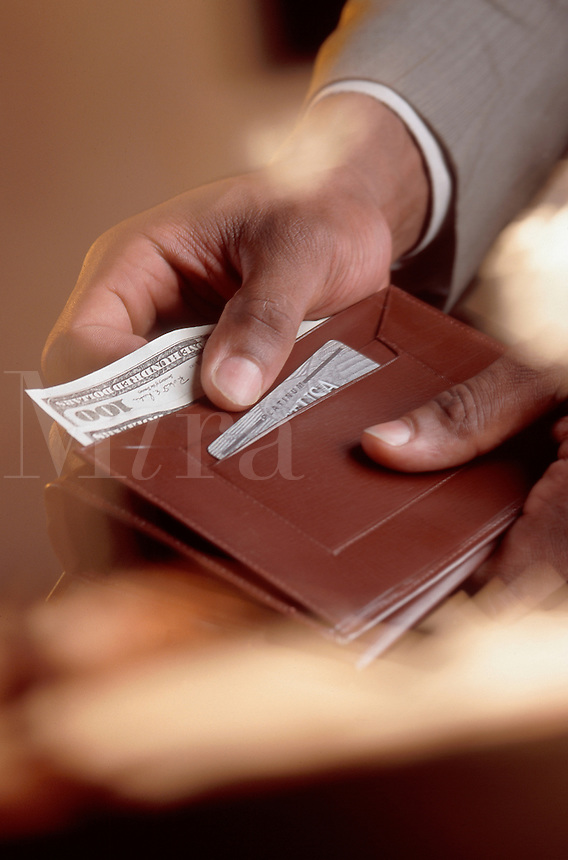 A businessman holding a wallet with $100 dollar bills.