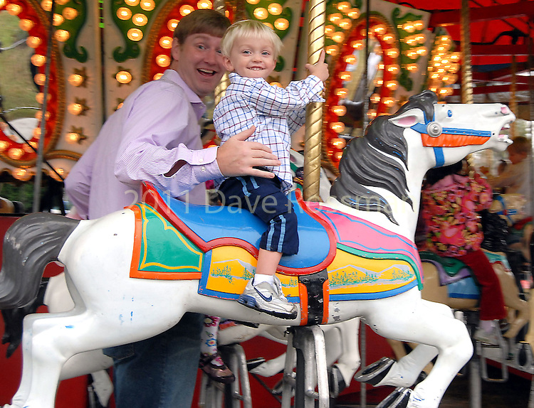 Kyle Carter and his son Caleb,2, ride the carousel at the Lanier Law Firm's Holiday Bash Sunday Dec. 13,2009.(Dave Rossman/For the Chronicle)