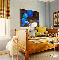 In this boy's bedroom an Empire-style boat bed is heaped with cushions, teddy bears and bolsters in a  fabric of brown and ochre stripes echoed in the Roman blind at the window