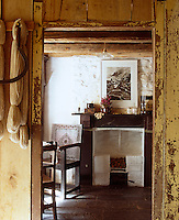A glimpse of the simple fireplace in the parlour through a wooden doorframe