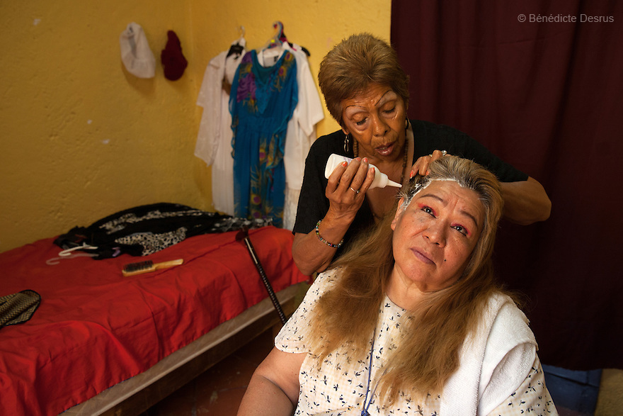 Luchita, a resident of Casa Xochiquetzal, colors Juanita's hair at the shelter in Mexico City, Mexico on May 25, 2016. Casa Xochiquetzal is a shelter for elderly sex workers in Mexico City. It gives the women refuge, food, health services, a space to learn about their human rights and courses to help them rediscover their self-confidence and deal with traumatic aspects of their lives. Casa Xochiquetzal provides a space to age with dignity for a group of vulnerable women who are often invisible to society at large. It is the only such shelter existing in Latin America. Photo by Bénédicte Desrus