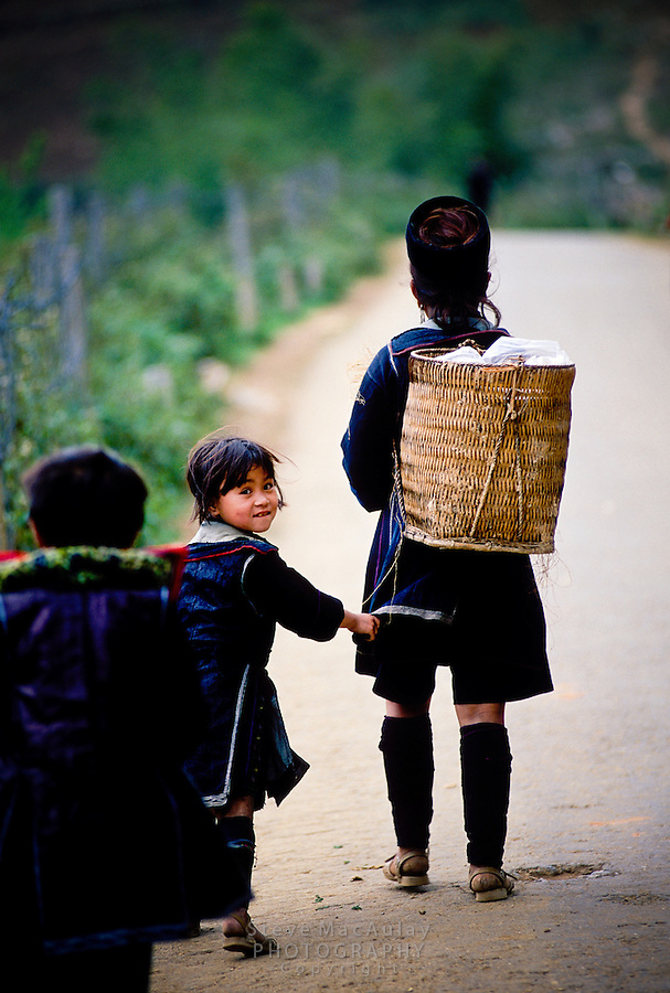 A curious young Black H'mong girl walking with her mother, Sapa, Vietnam