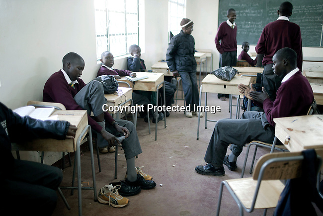ELDORET, KENYA - MAY 19: Eliud Kibet, age 18, changes to school shoes from running shoes in his class room at Kipkeino Highschool. He is promising long distance runner and he has already trained for an hour from 5.15 in the morning. Credit: Per-Anders Pettersson For Stern Magazine.