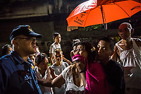 "MANILA, PHILIPPINES - OCTOBER 02: Elise Rufino, held by a family member, yessll at police as she grieves for her husband, Joselito Rufino Jumaquio, 52, who was killed by unidentified masked police, in what the police called an alleged ""buy bust"" operation on October 02, 2016 in Manila, Philippines. According to neighbors, at 9pm, at least 15 unidentified plain clothed police wearing masks, descended over the close railway side community quickly and silently. Roel, 13, Joselito's nephew, was playing a videogame with his uncle in small stall when the men grabbed his uncle and handcuffed him. They dragged the powerless pedicab driver towards the alleyway behind the stall and shouted at residents still gathered to go back into their homes and to turn their lights off. The residents then only reported what they heard. A woman's voice shouted ""He's fighting it out,"" or Nanlaban, a term used in many police reports to justify the use of lethal force. Two shots rang out - then 4 more. After the group left, neighbors discovered Joselito's bloodied body, a gun placed next to his handcuffed hands and a white plastic bag with methamphetamine. According to police, this was a legitimate buy bust operation where the handcuffed target drew a .38 calibre handgun and then, ""Sensing that his life was in serious danger, the lawman was constrained to fire back in order to protect his life against the armed aggressor."" After the men left they found Joselito handcuffed and found his body with a gun was placed next to him and a white plastic bag full of narcotics placed on his dead body. Elisa, Joselito's wife, arrived at the scene and started to confront police when she found out the news. Family and friends tried to restrain her but she continued. An angry crowd of residents gathered and started shouting at the police.""We curse you,"" they yelled, citing the countless times those arrested have been killed on the grounds that they were fighting back. ""You have no pity. We"