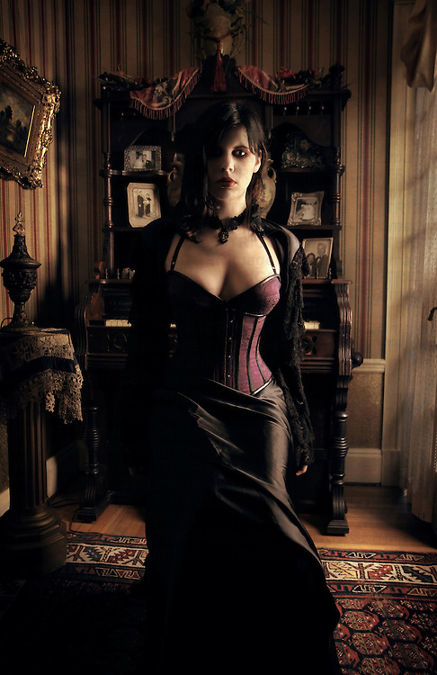 A young woman wearing a corset and black dress sitting in an Edwardian drawing room
