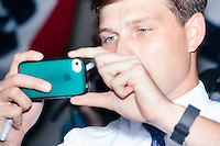 A campaign worker uses an iphone to take pictures as Republican presidential candidate and governor of Wisconsin Scott Walker meets people after speaking at a meet and greet with veterans at the Derry VFW in Derry, New Hampshire.