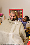 Preschool 4-5 year olds pretend play girl working on hair style of male teacher with blanket on him for a smock vertical