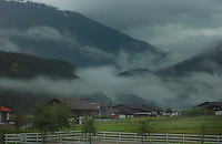 Farm buildings against a background of mist and mountains. Imst district, Tyrol/Tirol, Austria, Alps.